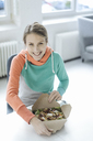 Portrait of laughing young woman having lunch in the office - JOSF02145