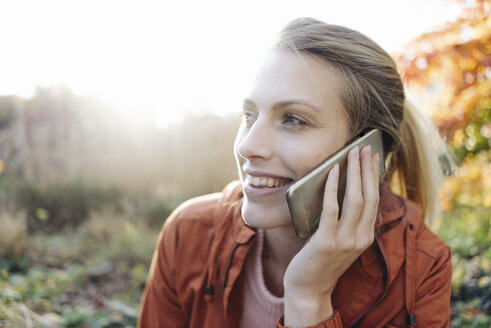 Portrait of young woman on the phone in autumnal park - JOSF02148