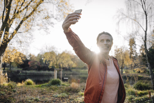Portrait of young woman taking selfie with cell phone in autumnal park - JOSF02154