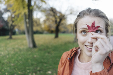 Portrait of young woman with  autumn leaf in a park - JOSF02157