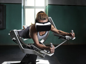 Woman wearing VR glasses using futuristic fitness machine - CVF00014