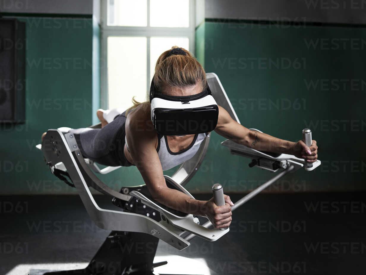 Woman wearing VR glasses using futuristic fitness machine - CVF00014 - Christian Vorhofer/Westend61