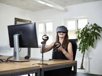 Happy woman wearing VR glasses at desk in office - CVF00017