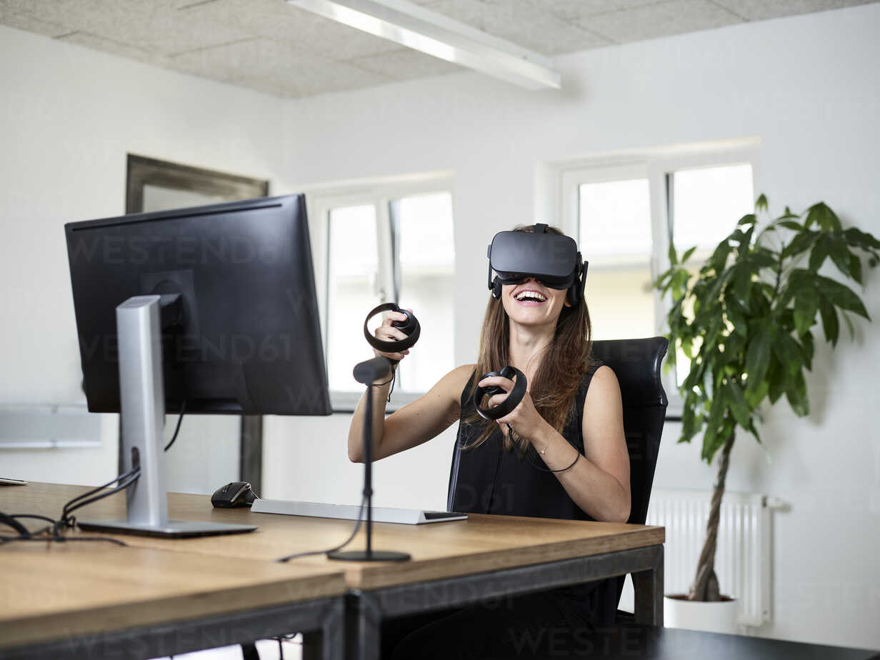 Happy woman wearing VR glasses at desk in office - CVF00017 - Christian Vorhofer/Westend61