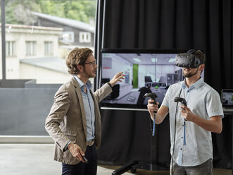 Man talking to colleague wearing VR glasses in front of screen - CVF00020