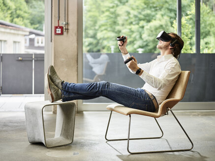 Man wearing VR glasses sitting on chair - CVF00023