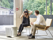 Man looking at woman wearing VR glasses sitting on chair - CVF00026