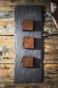 Three homemade brownies on slate - GIOF03755