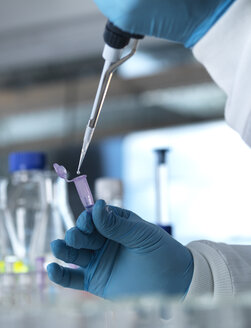 Scientist pipetting a DNA sample into a eppendorf tube for genetic testing in a laboratory - ABRF00014