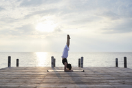 Young woman practicing yoga on a jetty by the sea at sunset - IGGF00390
