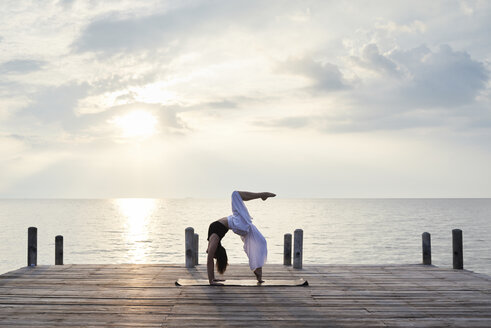 Young woman practicing yoga on a jetty by the sea at sunset - IGGF00393