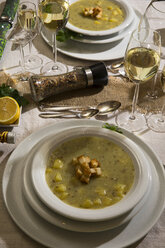Garlic cream soup with croutons on festive laid table - MAEF12483