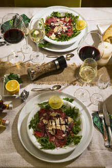 Beef carpaccio on rocket on festive laid table - MAEF12486