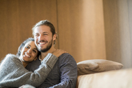 Portrait of happy young couple sitting on the couch - FMKF04682