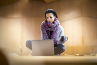 Portrait of fashionable young woman with cup of coffee sitting on conference table using laptop - FMKF04691