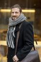 Portrait of man wearing scarf in autumn - FMKF04697