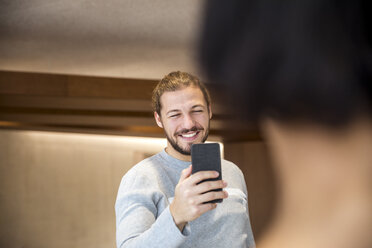 Portrait of smiling man taking picture of his girlfriend - FMKF04700