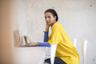 Portrait of young woman wearing yellow pullover using laptop - FMKF04709