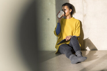Young woman wearing yellow pullover sitting on the floor drinking coffee to go - FMKF04712