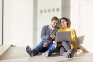 Portrait of laughing young couple sitting on the floor using laptop - FMKF04715