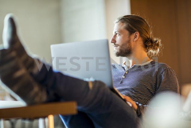 Portrait of pensive young man using laptop - FMKF04718 - Jo Kirchherr/Westend61
