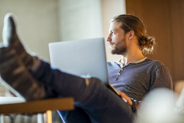 Portrait of pensive young man using laptop - FMKF04718
