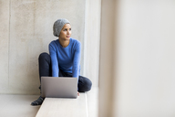 Portrait of young woman with laptop sitting on window sill looking out of window - FMKF04724