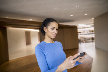 Portrait of young woman looking at cell phone - FMKF04733