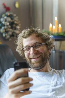 Portrait of happy man with smartphone at home at Christmas time - LAF01960