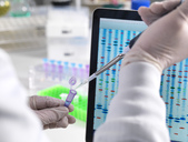 Scientist pipetting a DNA sample with the results on a computer sceeen in a laboratory - ABRF00024