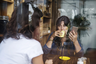 Woman with friend in a cafe holding smartphone and drinking coffee - SBOF01184