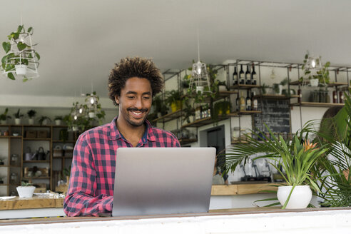 Smiling man using laptop in a cafe - SBOF01190