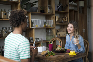 Smiling couple enjoying a meal together in cozy restaurant - SBOF01193