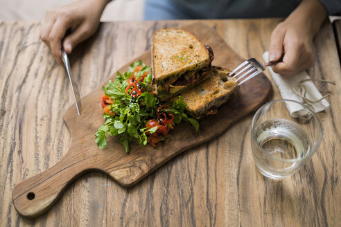 Hands holding knife and fork at wooden table with decorated salad and crusty bread - SBOF01196