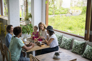 Friends with child socializing in cozy cafe - SBOF01205