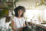 Portrait of woman with black hat behind the bar in a cafe - SBOF01208