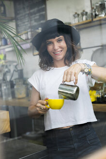 Portrait of woman with black hat behind the bar preparing a coffee - SBOF01211