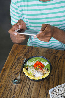 Male hands taking a picture of smoothie bowl with smartphone - SBOF01214