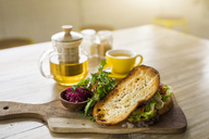 Crusty bread with green salad and beetroot on wooden plate and green tea in cafe - SBOF01220