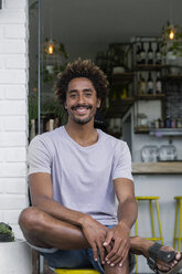 Portrait of smiling man sitting in front of a cafe - SBOF01235