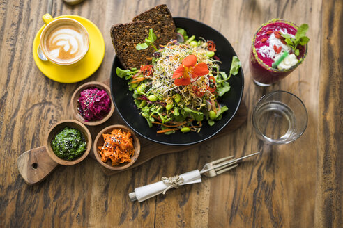 Decorated colorful salad on wooden plate with coffee, water and smoothie on the side - SBOF01244