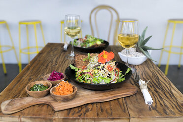 Decorated salad bowls on wooden table with glasses of wine - SBOF01250