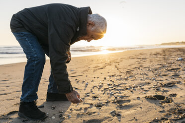Senior man strolling at the beach, collecting shells - JRFF01522