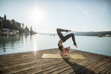 Woman practicing yoga on jetty at a lake - DAWF00577