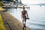 Rear view of woman in sportswear walking with yoga mat at lakeshore - DAWF00583