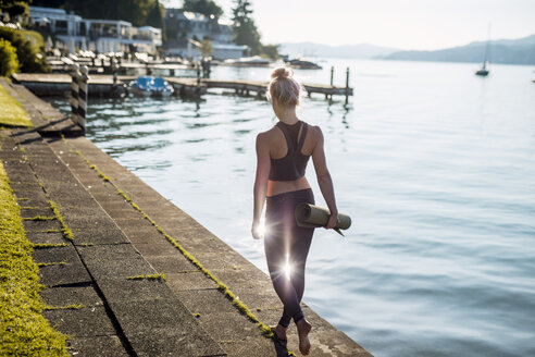 Rear view of woman in sportswear walking with yoga mat at lakeshore - DAWF00583