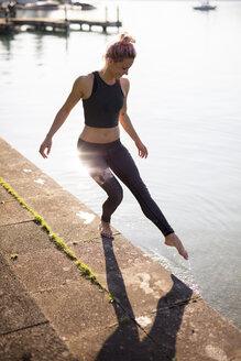 Woman in sportswear at lakeshore holding foot into water - DAWF00586