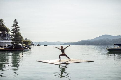 Woman practicing yoga on raft in a lake - DAWF00589