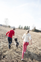 Man and woman with dog running on field - ECPF00178