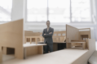 Miniature businessman figurine standing in architectural model - FLAF00117